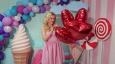 lolipop : Cute funny girl in pink striped dress with red gel balloons at candy party.