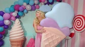macaroons : A charming girl in a pink dress with long blond hair is holding a huge colorful ice cream in the studio decorated with a bunch of different sweets. Candy girl.