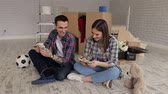 karton : A young couple sits on the floor in their new apartment among boxes and count the money.