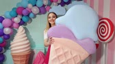 macaroons : A cute happy girl holds a giant plastic ice cream in her hands offering it to you. Cute style. The girl is a sweet tooth. Sweet shop. Stock Footage
