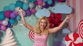 throws up : A happy young girl in striped pink dress throws up a multicolored tinsel at a party. Slow motion. Celebration. Birthday. Candy party. Stock Footage