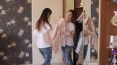 tentação : Girls get clothes from the closet and measure it in front of the mirror. Funny girls choose and measure clothes in front of the mirror.