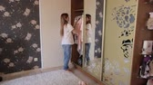 tentar : A young fashionable girl tries on a pink jacket at home in the bedroom near the cupboard with a large mirror.