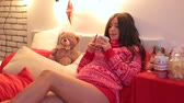 камин : Young pregnant girl in a red knitted sweater lies with a cup of tea on the bed against the backdrop of a Christmas tree. Pregnant girl with a cup of tea on New Years Eve. Стоковые видеозаписи