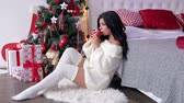 harisnya : Sexy girl in a warm knitted sweater with bare feet drinking tea sitting on the floor near the Christmas tree in the bedroom. Stock mozgókép