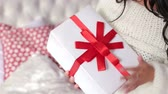 suéter : Close-up of the girl holding a white gift box with a red bow. The concept of the celebration and gifts. Christmas or new year gift in the hands of the girl. Vídeos