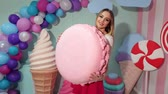 lolipop : A slender beautiful girl poses in the Studio with a big marshmallow in her hands. Happy candy girl with a big marshmallow on a background of balloons and a huge candy on stick.