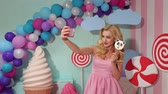 lolipop : A beautiful young blonde in a pink dress makes a selfie with a big Lollipop in her hands against the background of huge sweets, ice cream, candy and marshmallows. Stok Video