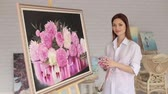 портфель : A talented girl artist is admiring her painting in the drawing studio. Portrait of an artist girl near a picture with flowers of peonies.