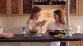 opatrný : Two young beautiful girls prepare a vegetable salad in the kitchen, have fun talking and laughing. Two sisters prepare a salad of tomatoes and cucumbers in the kitchen in the morning.