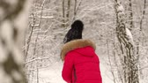 śnieżka : Close-up girl takes snow and throws it at someone. Cheerful girl playing snowballs in the woods. Wideo