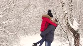 apaixonado : A happy man in love lifts his wife in the park among a multitude of snow-covered trees. A loving happy couple is walking in the park in the winter.