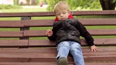 zneužívání : Close-up of a sad little boy of five years in a black jacket sitting on a bench in a park, the background is blurred.