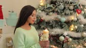Новая Англия : Young pregnant girl in green knitted sweater sits with a candle on the background of a Christmas tree with closed eyes and makes a wish. Стоковые видеозаписи