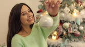 enjoying : A happy girl in a warm sweater is holding a Christmas ball on the background of a decorated Christmas tree. Stock Footage