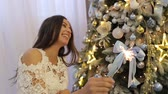 calcinhas : Portrait of happy pregnant girl near Christmas tree with Bengal lights. Laughing pregnant girl with a Sparkler near the Christmas tree. Christmas decor.
