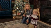 bengália : Close-up of mom with blonde long hair playing and having fun with her little son near the Christmas tree, they are holding sparklers. Stock mozgókép