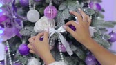 cobertor : Close-up of a girl decorating a Christmas tree, she hangs a bow on the branch.