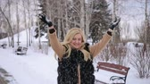 giymek : Beautiful happy young woman throwing snow and laughing, Happy beauty girl enjoying winter outdoors. Laughing model having fun in winter park. Stok Video