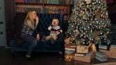 bom humor : Cheerful mother and son sit on the couch near the decorated Christmas tree and blow into the unfolding tube. Celebrating new year, Christmas or birthday. Birthday pipes. Party horn blower.