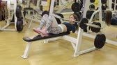 incentive : Sporty girl doing an exercise with a bar in the supine position in the gym. Stock Footage