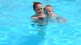 carinho : A young mother teaches her little son to swim in the pool in the summer on vacation. Happy little boy swimming in pool with mom. Slow motion.