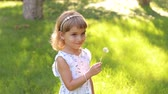 kolaylık : Happy child blowing dandelion flower outdoors. Girl having fun in spring park. Sunny portrait of cute little girl child blowing dandelion flower in summer day on the green grass.