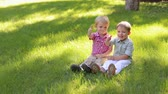 brother : Portrait of two cheerful boys five years old in the Park on the green bright grass, they show their thumb up.