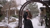 vampir : The bride in a black dress is embracing with the groom in a heavy snowfall in a wooden arch. Wedding. Bride in a black dress. Gothic wedding.