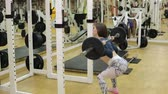 bunda : Young sexy girl in the gym doing squat with barbell in front of the mirror. Bodybuilding. Girl lifting weights in gym- squats with barbell.