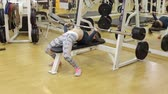 incentive : Sporty girl doing an exercise with a bar in the supine position in the gym. Girl bodybuilder. Stock Footage