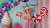 lízátko : Portrait of a cheerful and happy girl in a pink striped dress with a large candy in the form of a panda on the background of colorful balloons, a large plastic ice cream and candy. Dostupné videozáznamy