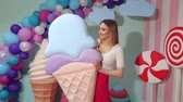lolipop : A cheerful cute girl holds a huge ice cream in the studio on a background of giant sweets. Barbie style. The girl is a sweet tooth. Stok Video