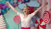 lolipop : A happy young girl in a white blouse and pink skirt throws up a multicolored tinsel at a party. Slow motion. Celebration. Birthday. Candy party.