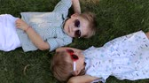 братья и сестры : Two small children in sunglasses, boy and girl are lying on the grass head to head. Portrait of two small children in sunglasses in the Park. The view from the top. Стоковые видеозаписи