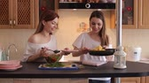 omelete : Two girls impose an omelet and vegetable salad of tomatoes and cucumbers in a plate. Two young girls making breakfast at home in the kitchen.