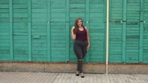 nagy : Sexy liberated girl with excess weight is leaning on a green fence, she is dressed in torn jeans and a t-shirt. Slow motion. Girl XXL.