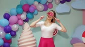 boneca : A young girl in bright clothes with lollipops in her hands in a studio with balloons, marshmallows and ice cream, she covers her eyes with big lollipops. Barbie style. Candy girl.