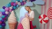 hatmi : A cheerful cute girl holds a huge ice cream in the studio on a background of giant sweets. Barbie style. The girl is a sweet tooth. Stok Video