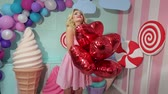 lolipop : Cute girl in pink striped dress with blonde curly hair holding a lot of red balls in the shape of hearts on the background of huge sweets. Barbie girl.