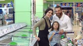 refrigerador : A young family with a child in the supermarket choose frozen foods. Portrait of a happy smiling family with a daughter near a large refrigerator in the supermarket. Slow motion.