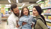 baby store : Young happy family are buying groceries in the supermarket. Mom dad and daughter buy sausage in the store, dad holds her daughter in his arms and they pretend that they bite the sausage. Slow motion.