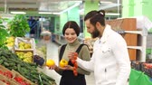 выборе : Shopping, food, sale, consumerism and people concept - happy couple buying pepper and tomatoes at grocery store or supermarket. Enjoying time in supermarket. Slow motion.