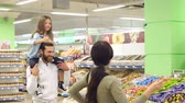 lolipop : Young fashionable parents buy sweets at the store, the daughter sits on the shoulders of her father and shows her thumb up. Portrait of a happy family in a supermarket. Slow motion.