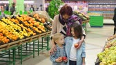 irmãos : Happy elderly woman with grandchildren in supermarket buys fruit. Portrait of grandmother of eighty years with her grandson and granddaughter in large modern supermarket buys of fruits and vegetables.