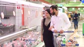 poskytování : Food, sale, consumerism and people concept - happy couple with shopping cart buying meat at grocery store or supermarket. Positive smiling family couple choosing chilled meat in food store.