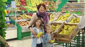 vnuk : Happy old woman with small children in the supermarket. Grandmother and grandchildren buy bananas in the store. Slow motion.
