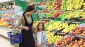 bakkaliye : Mother and daughter in produce section of supermarket. Woman and little girl choosing apple during shopping at fruit vegetable supermarket.Young mother and her daughter selecting fruits in supermarket