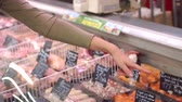 poskytování : Close-up of a girl chooses meat on the counter in the supermarket, close-up hand. A young woman buys fresh meat at the grocery store.