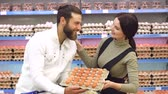 codorna : Portrait of a happy young couple in a supermarket with a box of chicken eggs. A young family buys eggs in a large supermarket. Shopping, food, selling, consumerism and people concept. Stock Footage